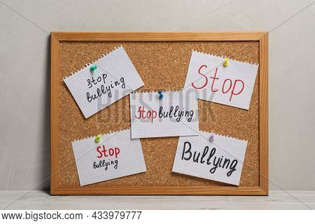 Notes With Phrase Stop Bullying Pinned To Cork Board On Table Near Grey Wall