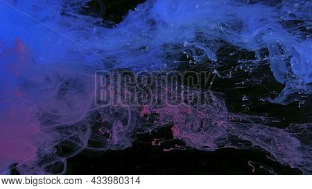 Colored Cloud Of Ink On A Black Background. Drops Of Pink And Blue Ink In Water. Pink And Blue Water