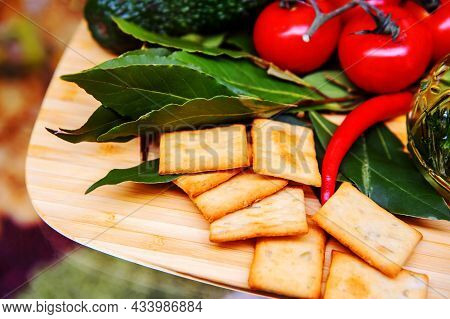 Crackers On A Wooden Board Decorated With Bay Leaf And Tomatoes. Salty Square Cookies On The Kitchen