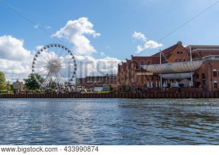 Ferris Wheel And Historic Buildings With City Sign On The Motlawa River In The Old Town Of Danzing