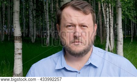 Face Of A Distressed And Sad Man, 35 Years Old, Dressed In A Blue Shirt On The Street With Emotions