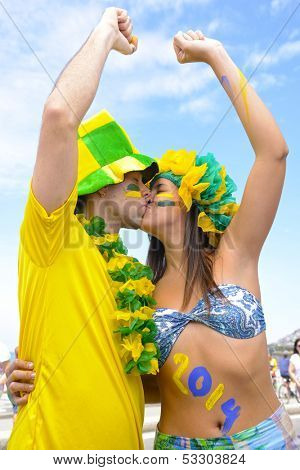 Happy couple of Brazilian soccer fans commemorating victory kissing each other.
