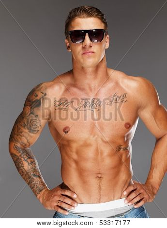 Man with tattooed muscular torso in blue jeans