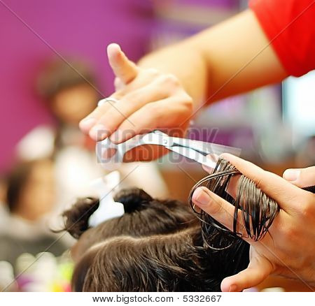 Hands holding scissors cutting hair in salon poster