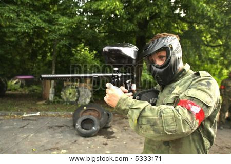 A paintball player in camouflage is aiming and shooting poster