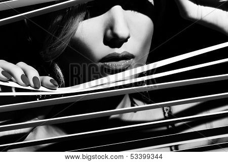 Woman peeking through the jalousie