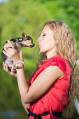 Young curly blond woman kissing little dog poster