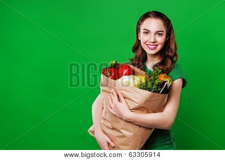 Young woman with a vegetables. on green background.