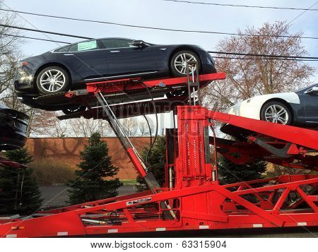 SPRINGFIELD, NJ - APRIL 14: New Model S cars lie on a truck outside a Tesla Service facility on April 14, 2014 in Springfield, NJ. On March 11th, NJ passed new rules banning direct-to-consumer sales.