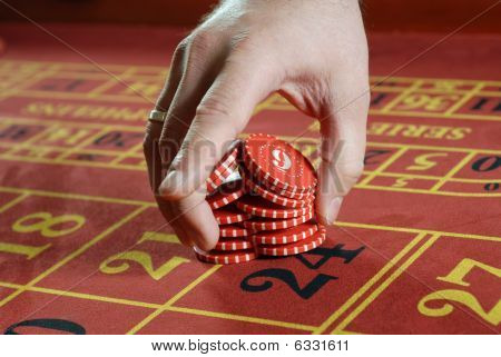 Male Hand Putting Red Poker Chips Into Game