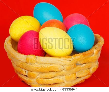 Baked basket with Easter colored eggs on a red background