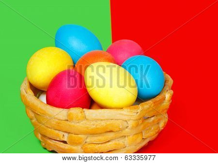 Baked Basket With Easter Colored Eggs On The Green And Red Background
