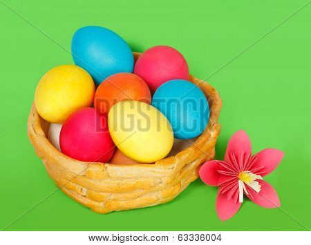 Baked basket with Easter colored eggs on a green background