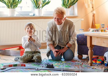 Grandmother And Little Grandson Playing With Racing Cars
