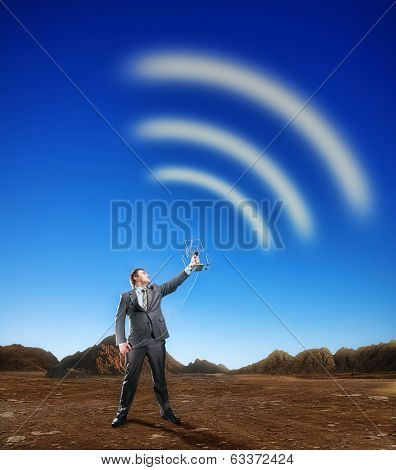 Businessman creating airwaves with antenna