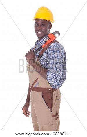 Young Happy Repairman Holding Wrench Over White Background poster