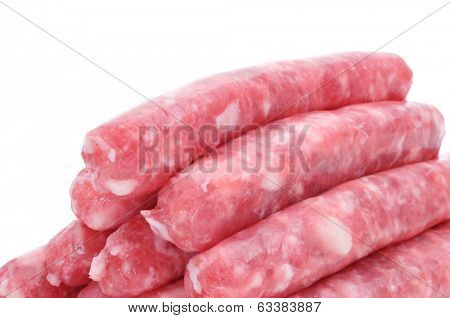 a pile of uncooked pork meat sausages on a white background