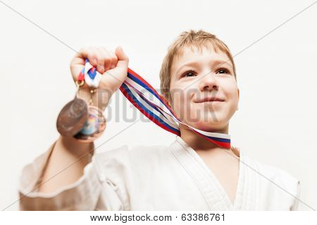 Martial art sport success and win concept - smiling karate champion child boy hand holding first place victory gold medal award