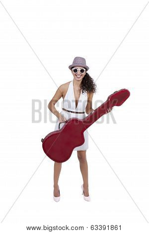 Happy young female wearing sunglasses posing with guitar
