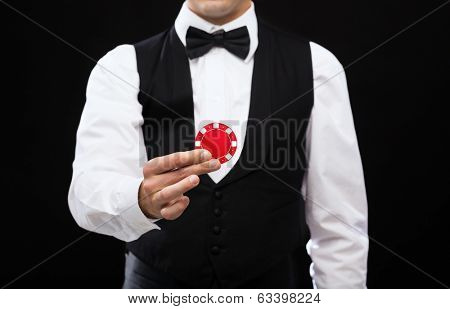 magic, performance, circus, casino and show concept - casino dealer holding red pocker chip