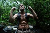 Survival man strong cheering in jungle rainforest. Muscular male survivor celebrating cheerful in forest at night showing muscles and aggressive survival instinct poster