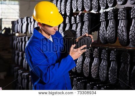 quality controller checking rubber-boots sole in storeroom