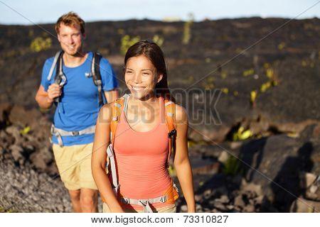 Hiking people - couple walking on lava field on Hawaii. Tourists hikers on hike near Kilauea volcano around Hawaii volcanoes national park, USA.
