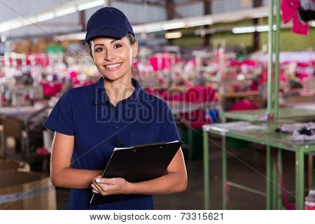 cheerful young clothing factory supervisor standing in production area
