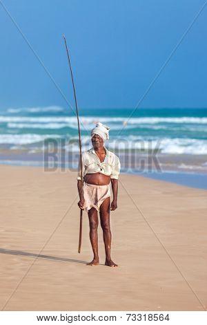 UNAWATUNA, SRI LANKA - MARCH 9, 2014: Elderly stilt fisherman at Hikkaduwa Beach. Most real stilt fishermen have been long gone. Today it's mainly young boys posing as stilt fishermen for tourists.