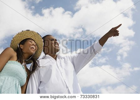 Multi-ethnic couple pointing and laughing