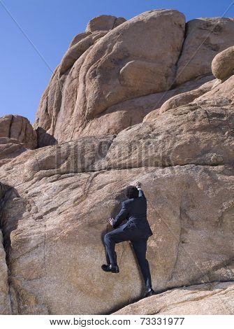 African businessman climbing rock