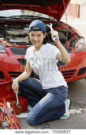 Asian woman fixing car