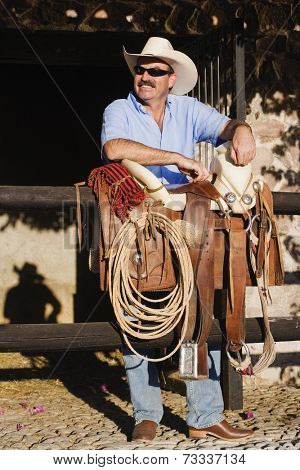 Hispanic man next to saddle