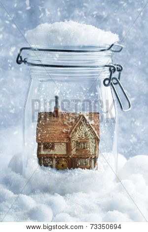 Country cottage snowglobe in retro kilner jar with cool tone effect