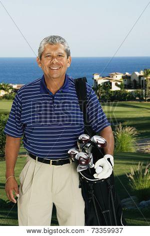 Hispanic man holding bag of golf clubs