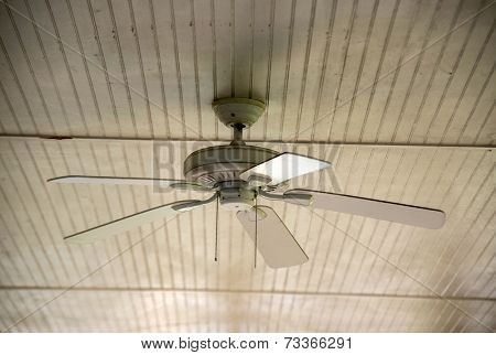 An old ceiling fan against a wooden siding