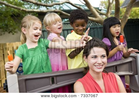 Young preschool children playing in daycare with teacher
