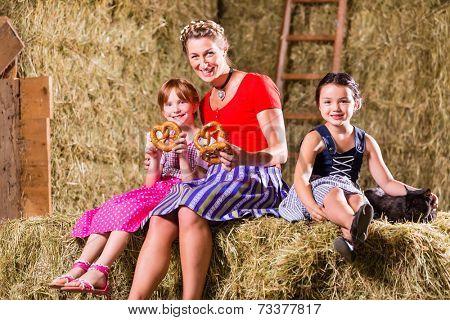 Bavarian mother and children sitting on hayloft with pretzels