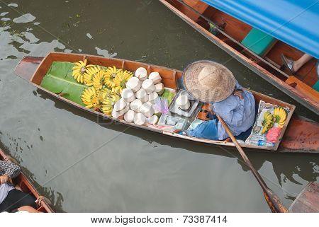 The woman sale fruits on boat at Damnoen Saduak Floating Market