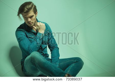 Close up picture of a young fashion man looking down while sitting on the floor with his thumb at his chin.
