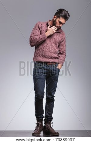 Full body image of an young fashion man looking down while scratching his beard, holding one hand in his pocket.