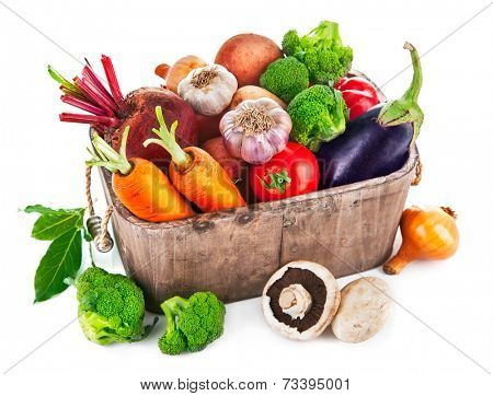 Harvest vegetables in wooden basket. Isolated on white background