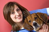 A veterinarian holding a beagle dog isolated over a red background. poster