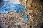 Old brick wall with the damaged blue-painted plaster. poster