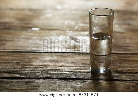 Glass of clean mineral water on rustic wooden planks background