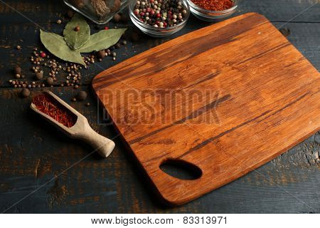 Different spices and herbs with cutting board on color wooden table background poster