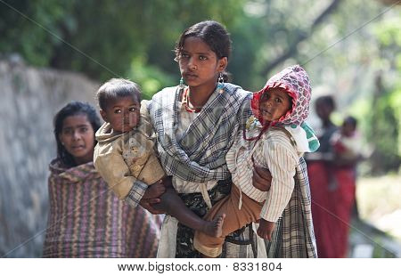 Young Nepalese Woman With Two Children Seeking Alms On The Street