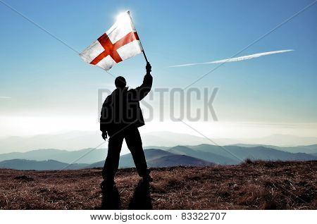 Winner holding high England flag on a peak
