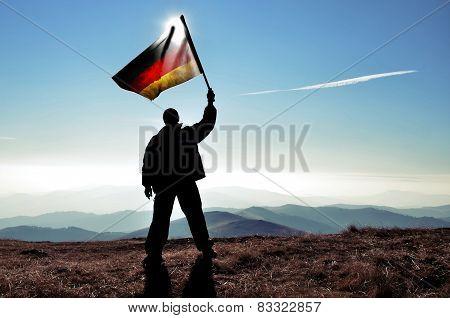 Man waving German flag on a mountain top