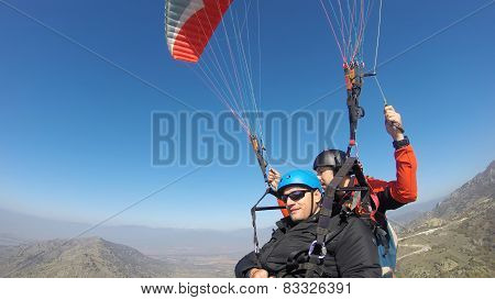 Tourist paragliding with a pilot guiding
